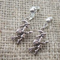 Silver witch on broomstick clip on earrings angle